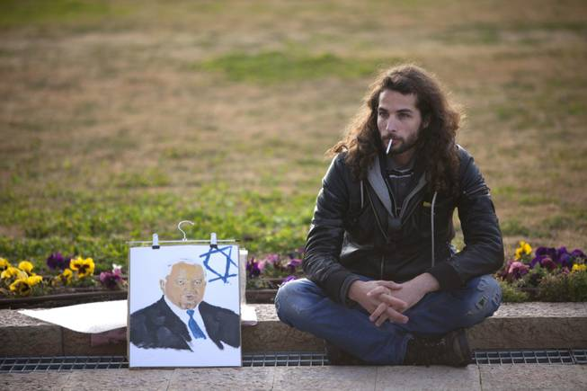 An Israeli man sits next to a painting of former Israeli Prime Minister Ariel Sharon near his coffin at the Knesset plaza, in Jerusalem on Sunday, Jan. 12, 2014. Sharon, the hard-charging Israeli general and prime minister who was admired and hated for his battlefield exploits and ambitions to reshape the Middle East, died Saturday, eight years after a stroke left him in a coma from which he never awoke. He was 85.