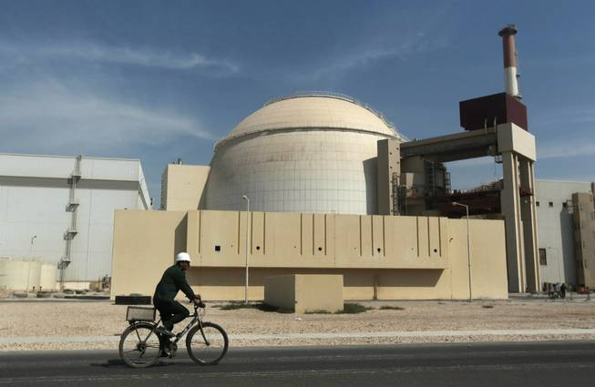 In this Oct. 26, 2010, file photo, a worker rides a bicycle in front of the reactor building of the Bushehr nuclear power plant, just outside the southern city of Bushehr. Iran and six world powers have agreed on how to implement a nuclear deal struck in November, with its terms starting from Jan. 20, officials announced Sunday.