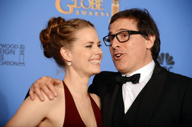 "Amy Adams and David O. Russell, winners of Best Motion Picture, Comedy or Musical, for ""American Hustle,"" celebrate in the press room at the 71st annual Golden Globe Awards at the Beverly Hilton Hotel on Sunday, Jan. 12, 2014, in Beverly Hills, Calif."