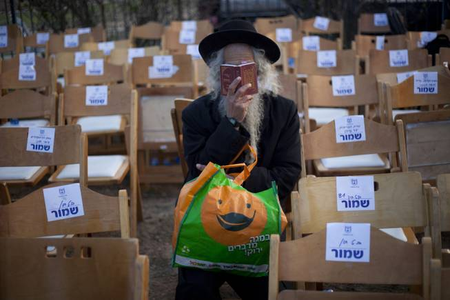 An ultra-Orthodox Jewish man reads from a payer book next to the grave of late Israeli Prime Minister Ariel Sharon, at the family farm near Sderot, southern Israel, Monday, Jan. 13, 2014.