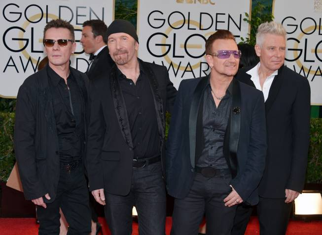 From left, Larry Mullen, Jr., The Edge, Bono and Adam Clayton, of the musical group U2, arrive at the 71st annual Golden Globe Awards at the Beverly Hilton Hotel on Sunday, Jan. 12, 2014, in Beverly Hills, Calif.