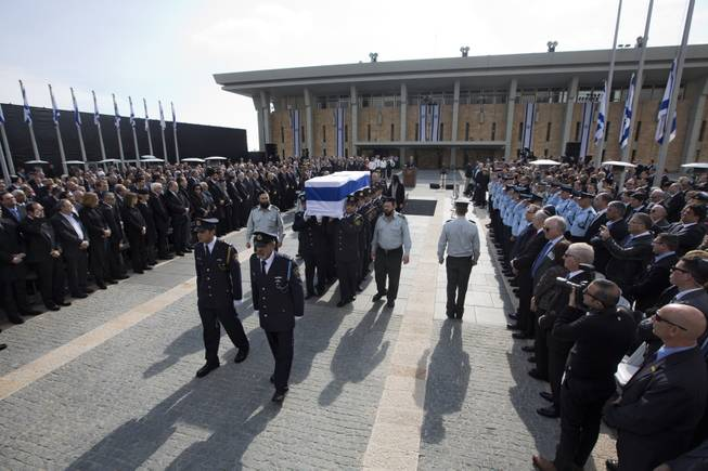 The coffin of late Israeli Prime Minister Ariel Sharon is carried after a memorial ceremony outside the Knesset, in Jerusalem, Monday, Jan. 13, 2014.