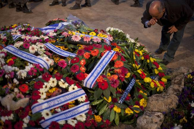 An man mourns next to the flower-covered fresh grave of late Israeli Prime Minister Ariel Sharon in Havat Shikmim near Sderot, southern Israel, Monday, Jan. 13, 2014.