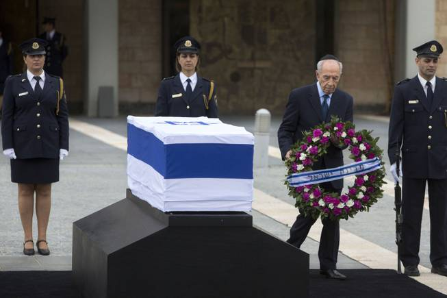 Israel's President Shimon Peres lays a wreath next to the coffin of late Israeli Prime Minister Ariel Sharon at the Knesset plaza, Israel's Parliament, in Jerusalem, Sunday, Jan. 12, 2014.