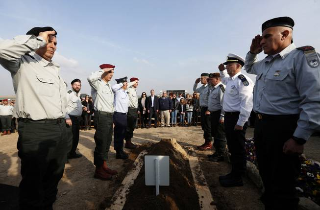 Israeli army officers salute as they stand over the grave of former Israeli Prime Minister Ariel Sharon during his funeral near Sycamore Farm, Sharon's residence in southern Israel, Monday, Jan. 13, 2014.
