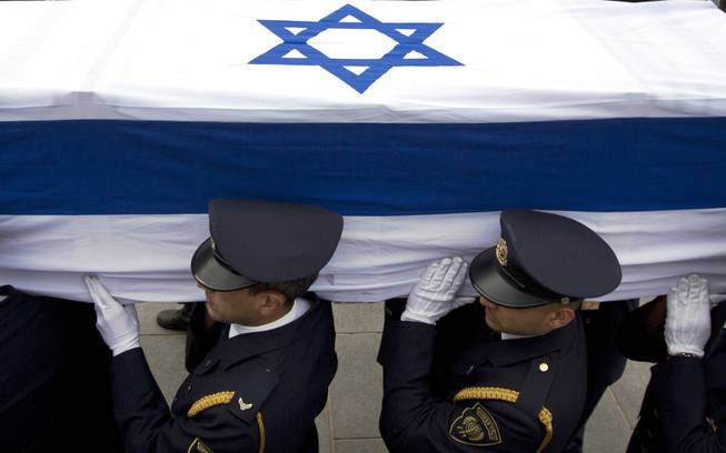 Members of the Knesset guard carry the coffin of late Israeli Prime Minister Ariel Sharon at the Knesset, Israel's Parliament, in Jerusalem, Sunday, Jan. 12, 2014.