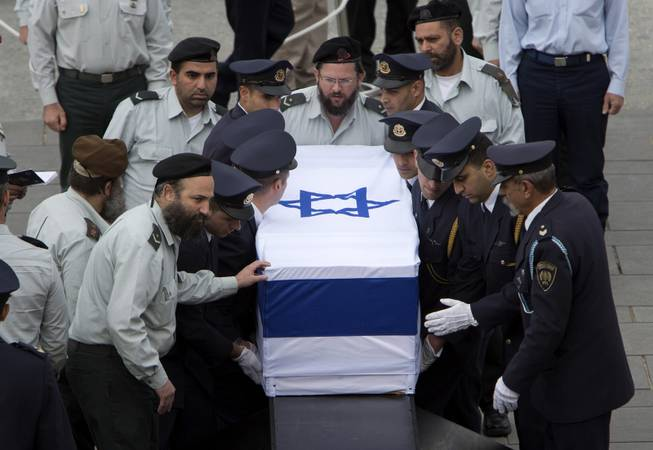Members of the Knesset guard carry the coffin of former Israeli Prime Minister Ariel Sharon at the Knesset plaza, in Jerusalem, Sunday, Jan. 12, 2014.