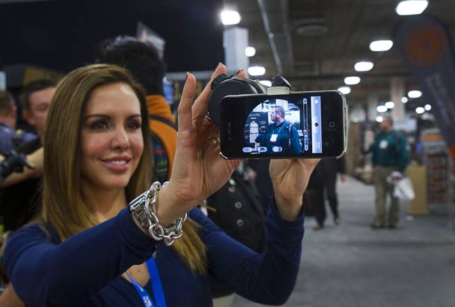 Michelle Peck holds an iPhone attached to a hunting scope at the iScope booth during the 2014 SHOT Show (Shooting, Hunting, Outdoor Trade) at the Sands Expo & Convention Center Tuesday, Jan. 14, 2014. The iScope allows hunters a full screen view of the target with both eyes open and and the option of filming the hunt through the scope. The iScope retails for $99.99.