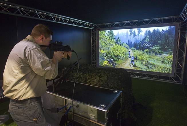 Mark Schneider of Maryland tries out a the Thales Saggitarius Evolution, a tactical small arms training simulator, during the 2014 SHOT Show (Shooting, Hunting, Outdoor Trade) at the Sands Expo & Convention Center Tuesday, Jan. 14, 2014. The French company markets the trainer to military and law enforcement agencies, a representative said.