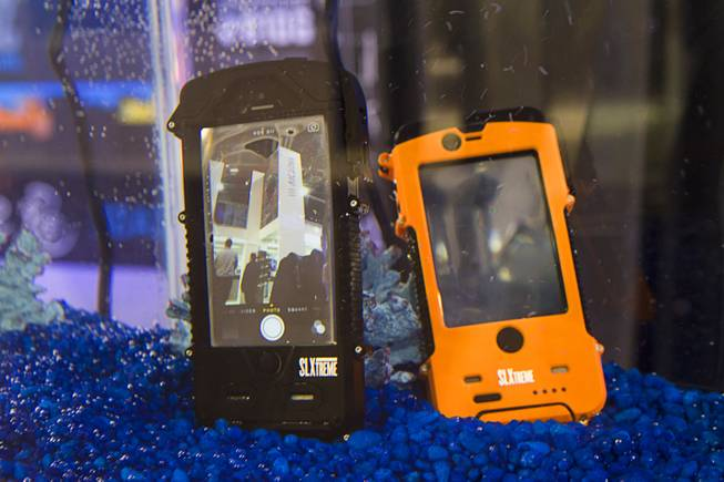 Smartphones with SL Xtreme SnowLizard cases are displayed in an aquarium during the 2014 SHOT Show (Shooting, Hunting, Outdoor Trade) at the Sands Expo & Convention Center Tuesday, Jan. 14, 2014. The cases also include an internal battery and solar charging panels on the back. The cases range in price from $129.95 to $149.99. An iPad case is expected to be available in March.