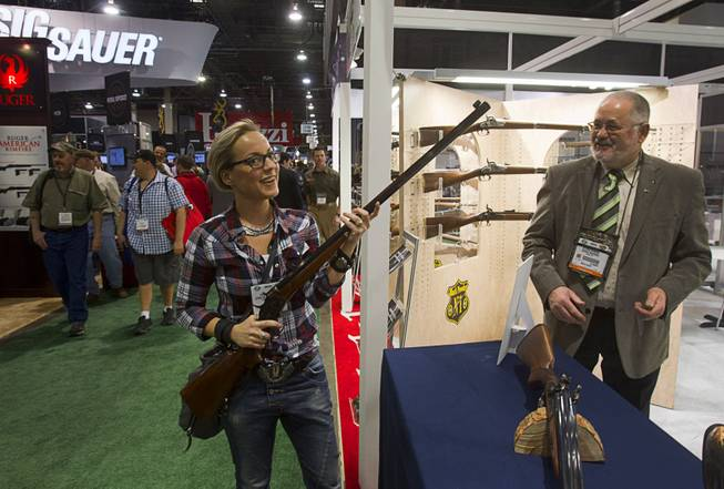 Yvonne Elendt of Germany holds a replica of an 1870's  Rolling Block John Bodine rifle at the Davide Pedersoli & Compny booth during the 2014 SHOT Show (Shooting, Hunting, Outdoor Trade) at the Sands Expo & Convention Center Tuesday, Jan. 14, 2014. The Italian company makes reproductions of classic firearms.