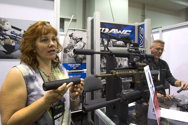 Bonnie DiCarlo explains the features of an AWC silencer to an attendee (not pictured) during the 2014 SHOT Show (Shooting, Hunting, Outdoor Trade) at the Sands Expo & Convention Center Tuesday, Jan. 14, 2014. Despite their military and Hollywood hitman reputations, silencers are often used by civilians to reduce recoil and noise, a representative said.