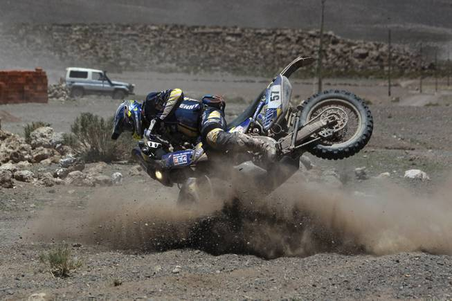 Yamaha rider Bruno Da Costa of France falls from his bike during the eighth stage of the Dakar Rally between the cities Uyuni, Bolivia and Calama, Chile in Kui, Bolivia, Monday, Jan. 13, 2014.