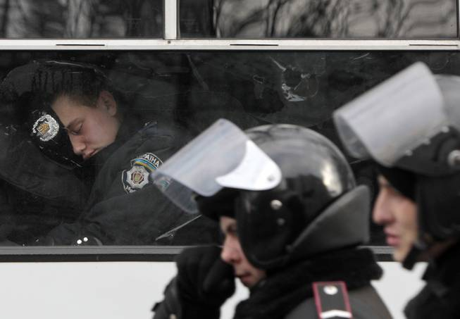 A police officer sleeps in a police van near of the Ukrainian Parliament in Kiev, Ukraine, in Kiev, Ukraine, Tuesday, Jan. 14, 2014. Organizers of the weeks-long anti-government protests are looking for a future strategy amid dwindling numbers and a continuing government crackdown on the protesters. The demonstrations, known as Euromaidan, were sparked by President Viktor Yanukovych's decision in November to freeze ties with the West and tilt toward Moscow. The pact was later sealed by a $15 billion bailout loan from the Kremlin.