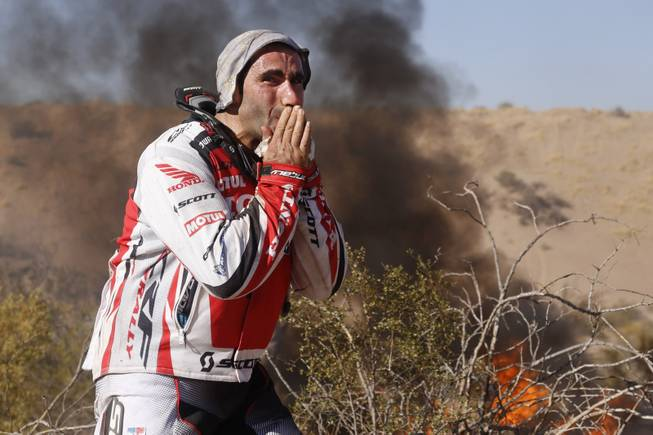 Honda rider Paulo Goncalves, of Portugal, cries as he watches his motorcycle burn during the fifth stage of the Dakar Rally between the cities of Chilecito and San Miguel de Tucuman, Argentina, Thursday, Jan. 9, 2014.