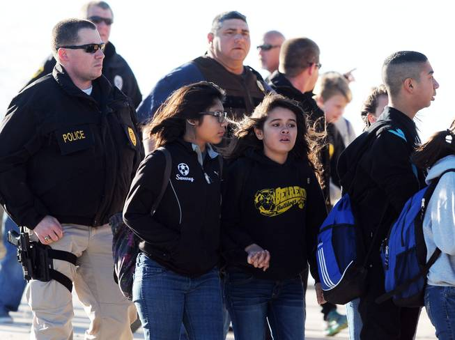 Students surrounded by officials are escorted from Berrendo Middle School after a shooting, Tuesday, Jan. 14, 2014, in Roswell, N.M.