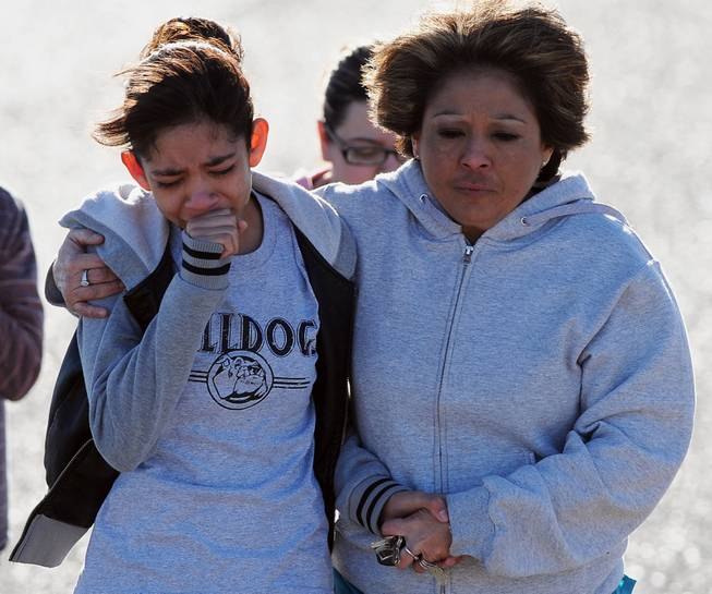 A student, left, is hugged after being united with families following a shooting at Berrendo Middle School, Tuesday, Jan.14, 2014, in Roswell, N.M.