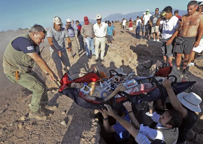 Dakar Rally Director Etienne Lavigne, left, helps carry Suzuki rider Gilbert  Escale of Spain after suffering an accident during the fifth stage of the Dakar Rally between the cities of Chilecito and San MIguel de Tucuman, Argentina, Thursday, Jan. 9, 2014.