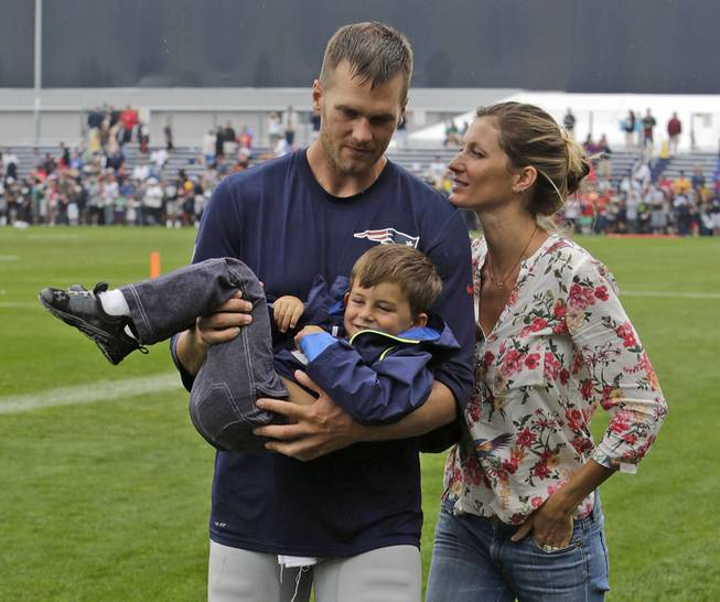 New England Patriots quarterback Tom Brady and his wife, Gisele Bundchen, with their son, Benjamin Brady, after a joint workout with the Tampa Bay Buccaneers at NFL football training camp in Foxborough, Mass., Tuesday, Aug. 13, 2013.