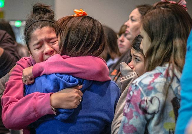 Thirteen-year-old Kimberly Macias cries as she sees schoolmates at a vigil for the victims, Tuesday, Jan. 14, 2014, in Roswell, N.M.