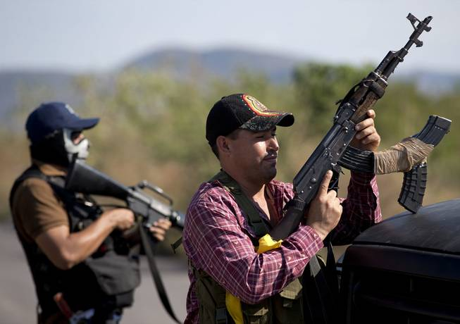 Armed men belonging to the Self-Defense Council of Michoacan stand guard at a checkpoint at the entrance of Antunez, Mexico, Tuesday, Jan. 14, 2014.