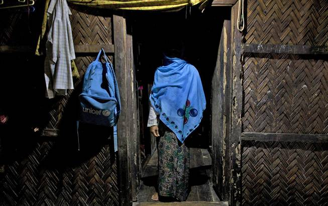 In this Sept. 15, 2013, photo, a woman who claims she was raped by Myanmar security forces stands in her home in Ba Gong Nar village, Maungdaw, northern Rakhine state, Myanmar.