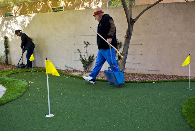 Curtis Murphy of Klean Scoop follows his fiance Melodie Harris as they clear a yard of dog poop that's complete with a putting green on Wednesday, Jan. 15, 2014.