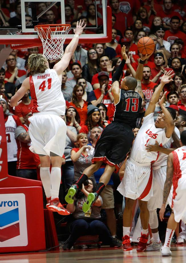 UNLV's Bryce Dejean-Jones attempts a shot over New Mexico's Alex Kirk, left, and Cleveland Thomas in the second half of an NCAA college basketball game Wednesday, Jan. 15, 2014 in Albuquerque, N.M. UNLV won 76-73.