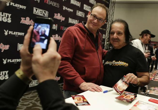 Porn star Ron Jeremy poses for a photo with a fan while signing autographs during the Adult Entertainment Expo, Wednesday, Jan. 15, 2014, in Las Vegas. Potential opportunities for X-rated film production in Nevada were the talk of the Expo at the Hard Rock hotel and casino this week, sparked by a Los Angeles law requiring male actors to wear condoms.