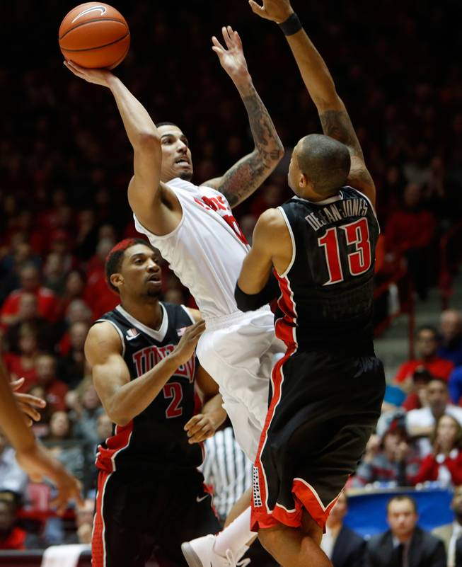New Mexico's Kendall Williams shoots over UNLV's Bryce Dejean Jones, right, and Khem Birch in the second half of an NCAA college basketball game Wednesday, Jan. 15, 2014 in Albuquerque, N.M. UNLV won 76-73.