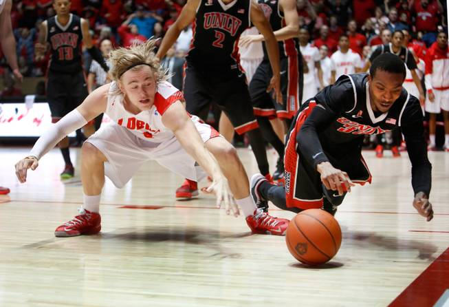 New Mexico's Hugh Greenwood, left, and UNLV's Deshawn Delaney hit the floor for a loose ball in the second half of an NCAA college basketball game Wednesday, Jan. 15, 2014 in Albuquerque, N.M. UNLV won 76-73.