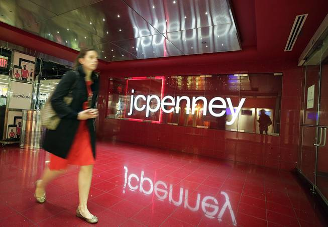 In this April 9, 2013 file photo, a customer leaves a J.C. Penney store in New York. J.C. Penney on Wednesday, Jan. 15, 2014 announced it will cut 2,000 jobs and close 33 stores as it tries to get back on the path to profitability.