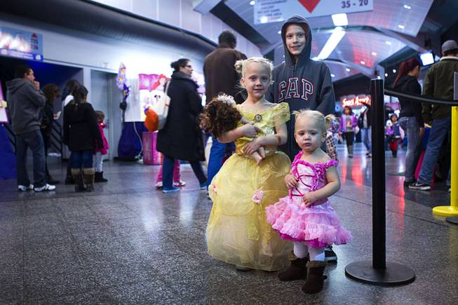 "Summer Breeze Morrison, 5, and Taylor Rayne Morrison, 18-months, pose in their princess dresses with their brother Brian Keith, 9,  before ""Disney On Ice: Rockin' Ever After"" at the Thomas & Mack Center Thursday, Jan. 16, 2014. The show plays at the center through Sunday."