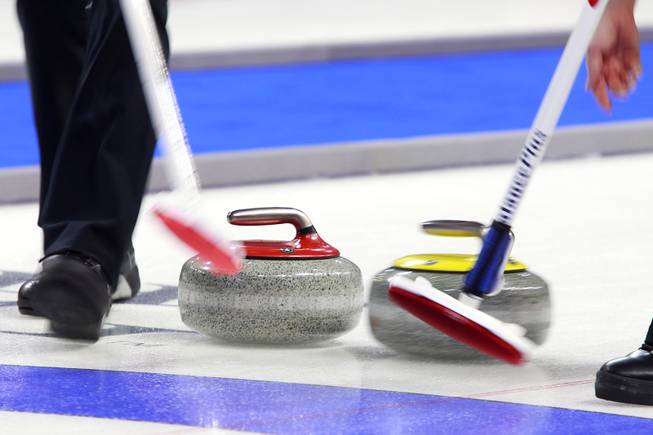 Sweepers try to position their stone during the first day of the 2014 World Financial Group Continental Cup of Curling at the Orleans Arena Thursday, Jan. 16, 2014. Of the twelve teams competing from around the world, nine of them will represent their respective country at the upcoming Olympics in Sochi, Russia.