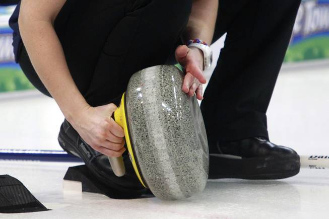 A curling athlete cleans the bottom of a stone before throwing it during the first day of the 2014 World Financial Group Continental Cup of Curling at the Orleans Arena Thursday, Jan. 16, 2014. Of the twelve teams competing from around the world, nine of them will represent their respective country at the upcoming Olympics in Sochi, Russia.