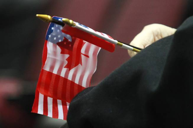 A fan holds a U.S. and Canadian flag during the first day of the 2014 World Financial Group Continental Cup of Curling at the Orleans Arena Thursday, Jan. 16, 2014. Of the twelve teams competing from around the world, nine of them will represent their respective country at the upcoming Olympics in Sochi, Russia.