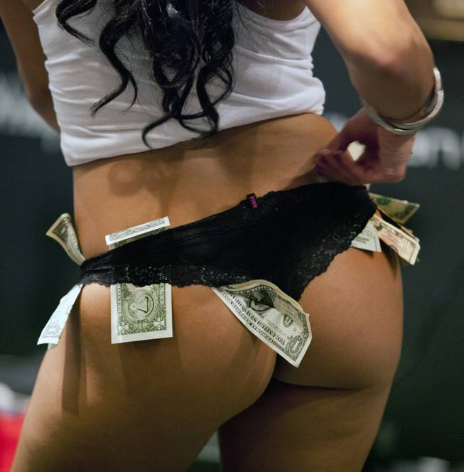 A pole dancer tucks another bill in her panties during the AVN Adult Entertainment Expo at the Hard Rock Hotel & Casino on Thursday, Jan. 16, 2014.