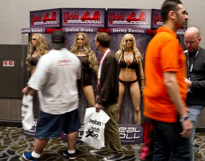Attendees walk past life-size dolls of porn stars during the 2014 AVN and Adult Entertainment Expo in the Hard Rock Hotel on Thursday, Jan. 16, 2014.
