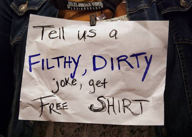 A vendor sports a funny sign around her neck at the AVN Adult Entertainment Expo in the Hard Rock Hotel & Casino on Thursday, Jan. 16, 2014.