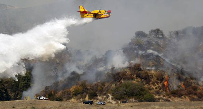 A firefighting plane makes a water drop on a wildfire that's burning in the hills just north of the San Gabriel Valley community of Glendora, Calif., on Thursday, Jan 16, 2014. Southern California authorities have ordered the evacuation of homes at the edge of a fast-moving wildfire burning in the dangerously dry foothills of the San Gabriel Mountains.