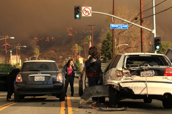 Motorists exchange information after a car accident as a wildfire burns in the hills just north of the San Gabriel Valley community of Glendora, Calif. on Thursday, Jan 16, 2014.