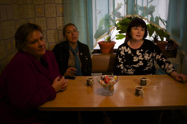 In this picture taken on Wednesday, Nov. 27, 2013, Alexandra Krivchenko, left, Nadezhda Kurovskaya, center, Irina Kharchenko, right, residents of 5a Akatsiy, street drink tea in the village of Vesyoloye outside Sochi, Russia.