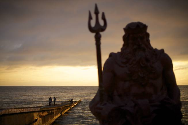 In this photo taken on Thursday, Nov. 28, 2013, the statue of ancient Roman god Neptune sits in guard of the beach during the sunset at an embankment of Sochi, Russia.