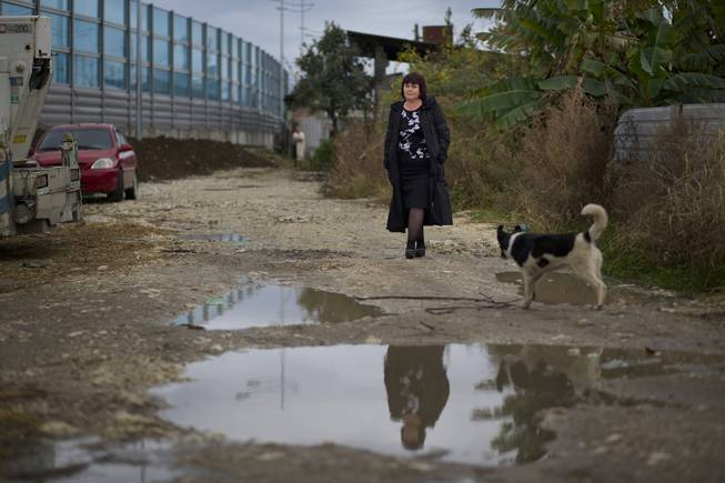 In this photo taken Wednesday, Nov. 27, 2013, Irina Kharchenko walks away from a screen separating the yard of her house and a federal highway in the village of Vesyoloye outside Sochi, Russia.