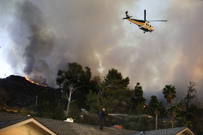 A helicopter carrying water flies over the residential area as a man sprays water on his home on Thursday, Jan. 16, 2014, in Azusa, Calif.
