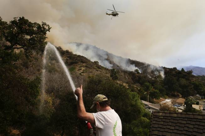 Mark Davis gives a thumb up toward a helicopter as he sprays water around his property on Thursday, Jan. 16, 2014, in Azusa, Calif.