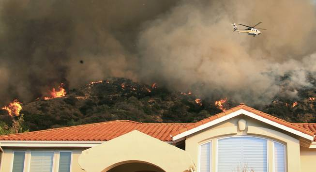 A firefighting helicopter passes over the hills behind homes as a wildfire burns just north of the San Gabriel Valley community of Glendora, Calif., on Thursday, Jan 16, 2014.