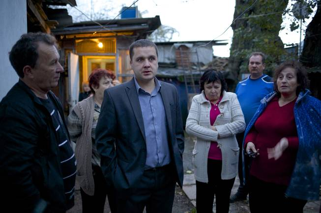 In this photo taken on Wednesday, Nov. 27, 2013, Igor Zarytovsky, center, and his father Vladimir, left, gather with their neighbors in the yard of the railroad house in the village of Vesyoloye outside Sochi, Russia.