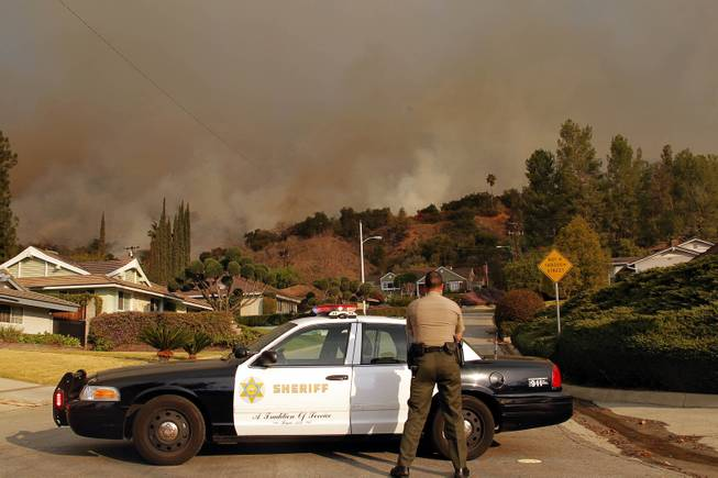An Los Angeles County Sheriff blocks a road in a neighborhood while a wildfire burns in the hills just north of the San Gabriel Valley community of Glendora, Calif., on Thursday, Jan 16, 2014.