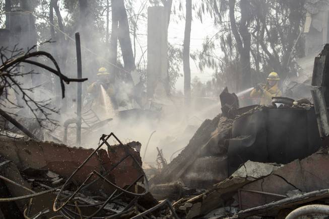 Firefighters put out hot spots at the Singer Mansion after it burned down during a wildfire burns just north of the San Gabriel Valley community of Glendora, Calif., on Thursday, Jan 16, 2014.
